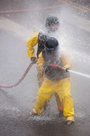 ouray: Men dressed in yellow firemen slickers and firehoses have annual Waterfight on July 4, Main Street, Ouray, CO, sponsored by Ouray Fire Department  Editorial