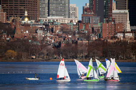 incidental people: Colorful docked sailboats and Boston Skyline in winter on half frozen Charles River, Massachusetts, USA