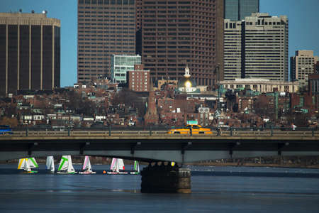 yellow taxi: Yellow Taxi drives across Harvard Bridge over Charles River with Colorful sailboats, Boston, Massachusetts, USA Stock Photo