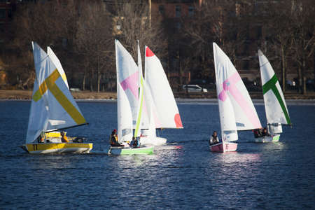 incidental people: Colorful sailboats and Boston Skyline in winter on Charles River, Massachusetts, USA