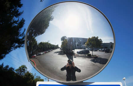 concave: Photographer in concave mirror photographs himself, Ventura, California, USA Stock Photo