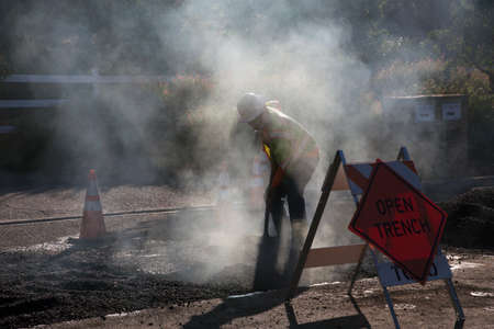 Roadworker repaves road with steam, Encino Drive, Oak View, California, USA Editorial