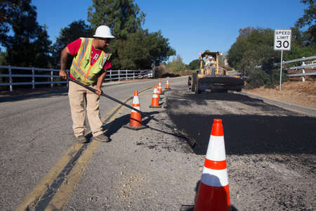 Roadworker repaves road with steam, Encino Drive, Oak View, California, USA 新聞圖片