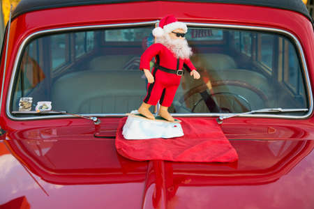 male likeness: Surfing Santa Clause on a vintage red car hood, California, USA