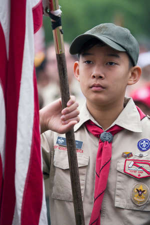 only one teenage boy: Asian boyscout display US Flag at solemn 2014 Memorial Day Event, Los Angeles National Cemetery, California, USA