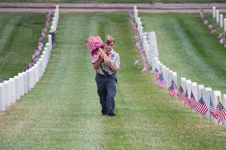 only one teenage boy: Boyscout places one of 85, 000 US Flags at 2014 Memorial Day Event, Los Angeles National Cemetery, California, USA