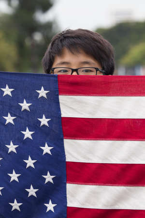 only one teenage boy: Korean American Boyscout and US Flag at 2014 Memorial Day Event, Los Angeles National Cemetery, California, USA Editorial