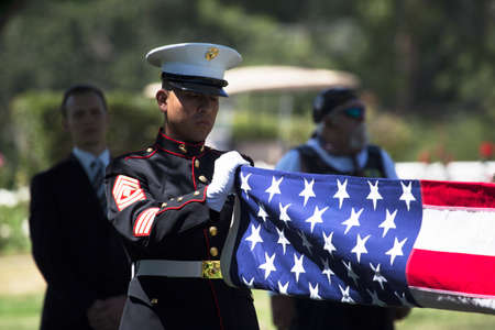 a memorial to fallen soldiers: Marine folds flag at Memorial Service for fallen US Soldier Editorial