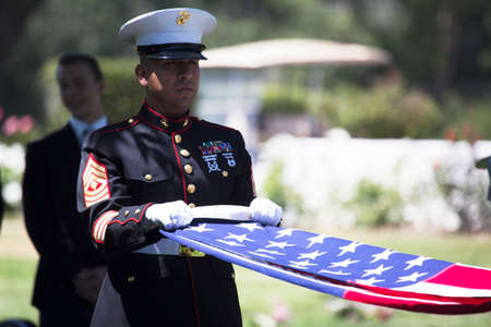 Marine folds flag at Memorial Service for fallen US Soldier 新闻类图片