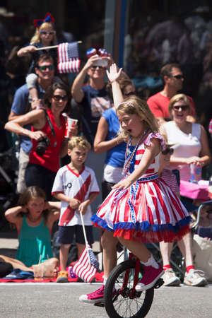 incidental people: Girl rides unicycle during July 4, Independence Day Parade, Telluride, Colorado, USA