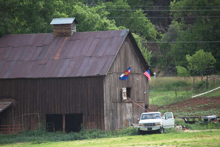 colorado flag: Colorado and US Flag hang on barn with white pickup truck, Colorado, USA