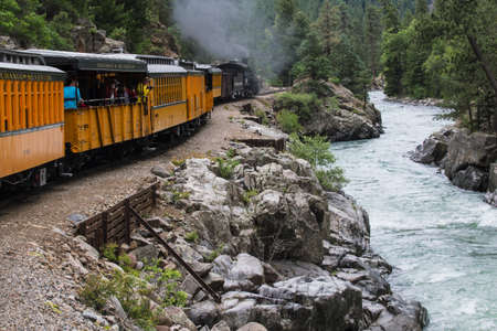 narrow gauge railroad: Durango and Silverton Narrow Gauge Railroad Steam Engine travels along Animas River, Colorado, USA