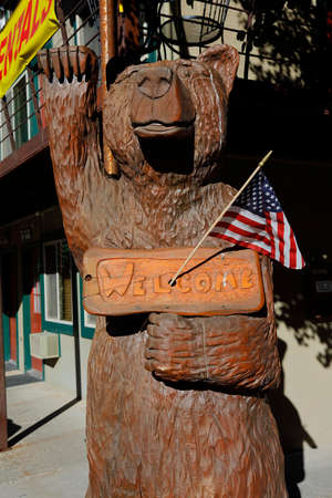 ouray: Carved wooden bear and US Flag waves with paw and Welcome Sign, Ouray, Colorado Editorial