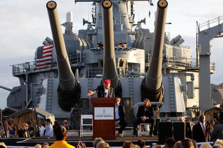 a battleship: SAN PEDRO, CA - SEPTEMBER 15, 2015: Donald Trump, 2016 Republican presidential candidate, speaks under large battleship guns during a rally aboard the Battleship USS Iowa in San Pedro, Los Angeles, California.