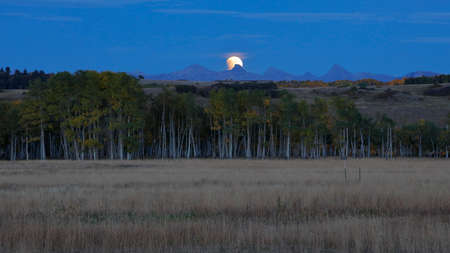 lunar eclipse: Lunar Eclipse moon over San Juan Mountains, Hastings Mesa with old western fence in foreground, San Miguel County, Colorado Editorial