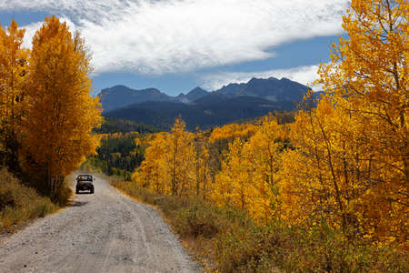 ouray: Jeep drives down backroad in San Juan Mountains In Autumn Colorado, near Telluride, Ouray and Ridgway in San Miguel County