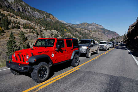 ouray: Red jeep and cars are delayed on Million Dollar Highway Route 550 out of Ouray Colorado during road repairs Editorial