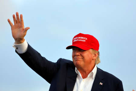 SAN PEDRO, CA - SEPTEMBER 15, 2015: Donald Trump, 2016 Republican presidential candidate, waves during a rally aboard the Battleship USS Iowa in San Pedro, Los Angeles, California while wearing a red baseball hat that says campaign slogan