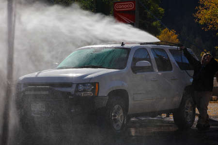 White SUV is cleaned in car wash in Ouray, Colorado with water splashing and flowing
