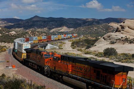 flatcar: Freight train with cargo containers winds its way through mountain landscape, California