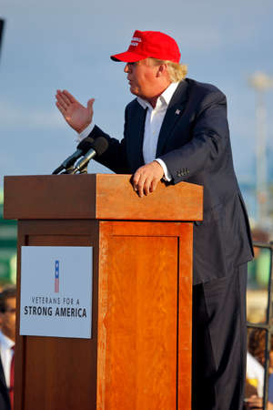 donald: SAN PEDRO, CA - SEPTEMBER 15, 2015: Donald Trump, 2016 Republican presidential candidate, speaks during a rally aboard the Battleship USS Iowa in San Pedro, Los Angeles, California while wearing a red baseball hat that says campaign slogan Make America G Editorial