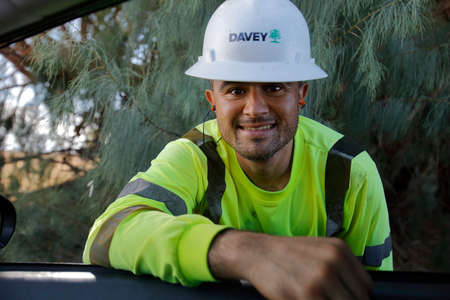 barstow: Utility worker in green shirt smiles while leaning into car, near Barstow, CA