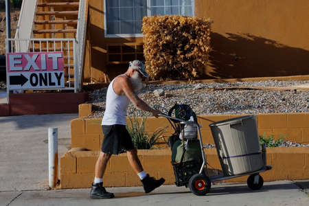 barstow: BARSTOW, CA, Homeless man in t-shirt and dog pushes a shopping cart containing his possessions down the side of the street.