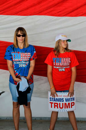 SACRAMENTO, CA - JUNE 01, 2016: Republican Presidential candidate Donald Trump female supporters agaist flag at a campaign rally in airport hanger in Sacramento, California