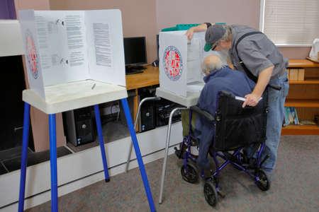encuestando: Condado de Ventura, CA - 7 DE JUNIO, 2016 - Varón mayor ayuda al hombre minusválido en el colegio electoral de Ventura para el Condado de Ventura primarias de California, California.