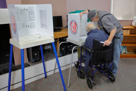 voting booth: VENTURA COUNTY, CA - JUNE 7, 2016 -- Senior male helps handicapped man at Ventura Polling Station for California primary Ventura County, California.