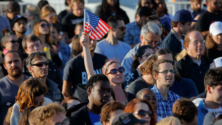 high school football: SANTA MONICA, CA - MAY 23, 2016: Female with US Flag is supporter of US Democratic presidential candidate Bernie Sanders (D - VT) at a Presidential rally at Santa Monica High School Football Field in Santa Monica, California.