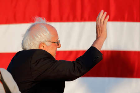 high school football: SANTA MONICA, CA - MAY 23, 2016: US Democratic presidential candidate Bernie Sanders (D - VT) profile and US Flag at Presidential rally at Santa Monica High School Football Field in Santa Monica, California.