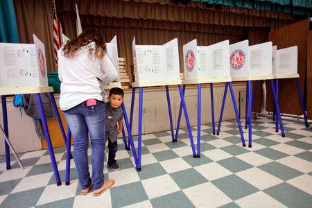 encuestando: Condado de Ventura, CA - 7 DE JUNIO, 2016 - El muchacho mira bajo cabina de votación en el colegio electoral de Ventura para el Condado de Ventura primarias de California, California. Editorial