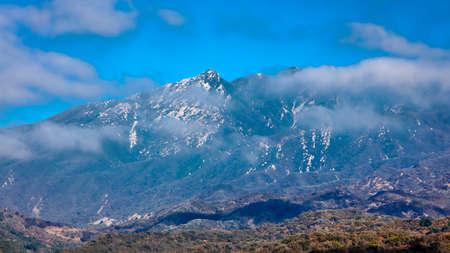 Clouds float by mountain top in Ojai California - view towards Santa Barbara, CA