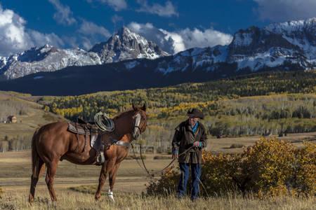 OCT 4, 2017, RIDGWAY COLORADO - Older Cowboy, Howard Linscott , leads packhorse across historic Last Dollar Ranch on Hastings Mesa, SW Colorado, San Juan Mountains