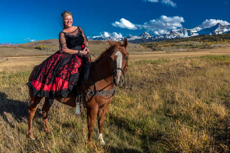 OCTOBER 2017, Ridgway, Colorado: Amanda wears Red Saloon Girl Western Costume on historic Last Dollar Ranch, Hastings Mesa Editöryel