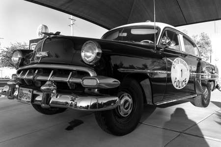 Kingman, Arizona, USA, July 2, 2018 - old Route 66, shows vintage Police Car and Gas Pump in black and white Foto de archivo - 112050115