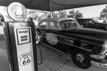 Kingman, Arizona, USA, July 2, 2018 - old Route 66, shows vintage Police Car and Gas Pump in black and white Foto de archivo - 112050121