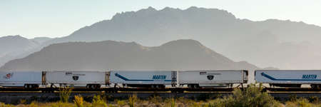 SEPT 13, 2013 - CALIFORNIA, USA - Freight train carries truck trailers under mountain near Needles California in American Southwest Editorial