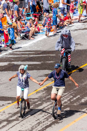 TELLURIDE, COLORADO, USA - July 4, 2018 - Annual  Independence Day Parade, Telluride, Colorado Colorado Avenue shows couple holding hands on Unicycles Foto de archivo - 111979647