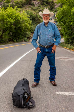 July 20, 2018, OURAY COLORADO, USA - Cowboy hitch hikes along route 550 outside of Ouray, Colorado