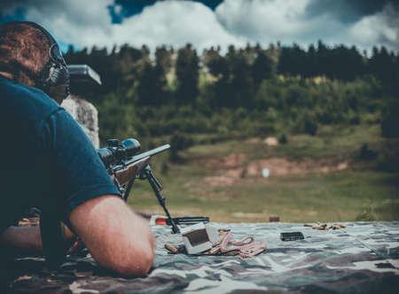 撮影範囲の長い銃身の銃を持つ男