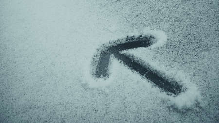 Arrow sign carved into snow