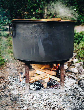 Traditional cuisine big black pot cooking food, natural fire with wood heating Reklamní fotografie
