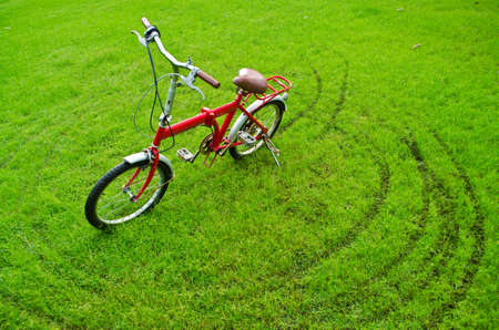 woman bike: the red bicycle on grass Stock Photo