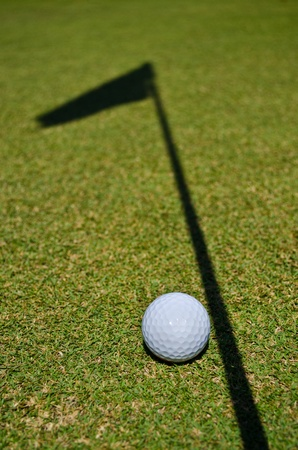 a golf ball and the shadow of the hole flag Stock Photo