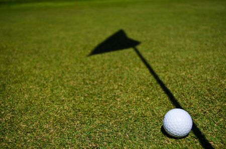 a golf ball and the shadow of the hole flag photo