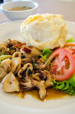 basil squid served with rice and egg in thailand photo