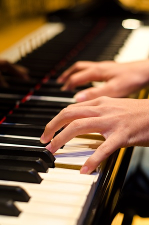 hand of a pianist playing on a piano photo