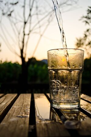 half: a glass of water in sunset background